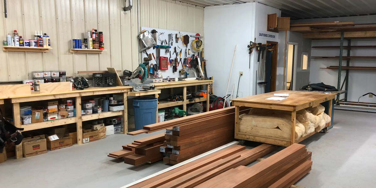 This photo of the brand new Sunspace Design workshop located in Hampton, New Hampshire features well-stocked shelves, a large workbench, and fresh mahogany boards