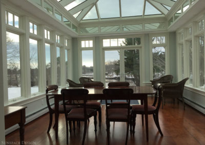 An elegant table with full seating area sits on the polished wood floors of a conservatory space with tall glass windows, French doors, and angular glass roof components