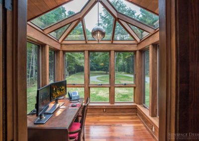 A polished wooden desk sits atop gorgeous wood floors in a conservatory office space featuring awning windows and a glass roof with angular mahogany framing