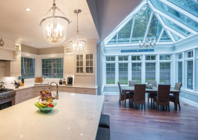 A beautiful marble-topped kitchen island is illuminated via warm overhead lighting on the left and a large glass conservatory dining area is lit via cool sunlight on the right