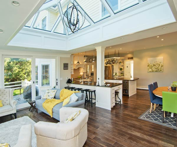 A photo of a Sunspace Design orangery-style double hip skylight element located beside an open concept kitchen than connects to a large entertainment area