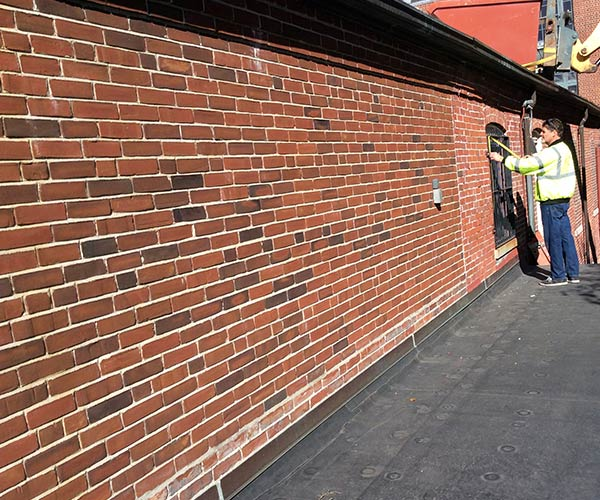 Construction workers measure an area along a red brick wall that marks the length of the upcoming glass roof and skylight system