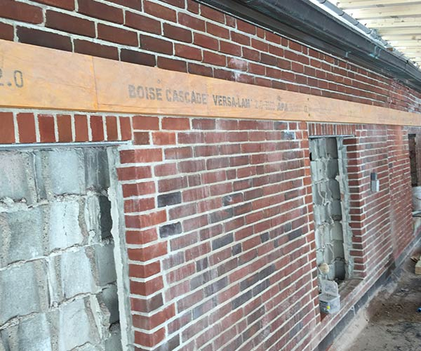 A LVL ledger has been installed along the length of a red brick wall in order to provide an attachment point for the new glass skylight system