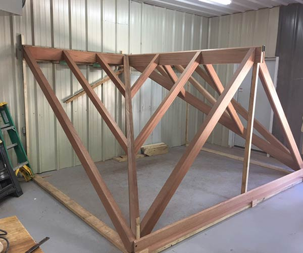 The center glass dormer section of a custom glass roof has been pre-assembled and framed in mahogany