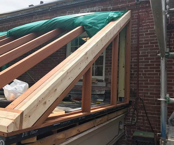 The right side gable end of Sunspace Design's custom glass roof bank entryway renovation project is visible in this photograph