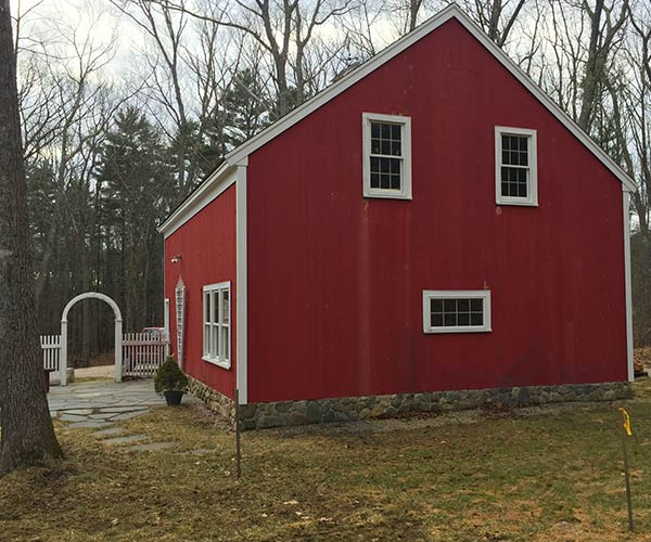 "A ""before"" photo of an area adjacent to a big red barn located in York, Maine upon which a custom greenhouse addition will be built"