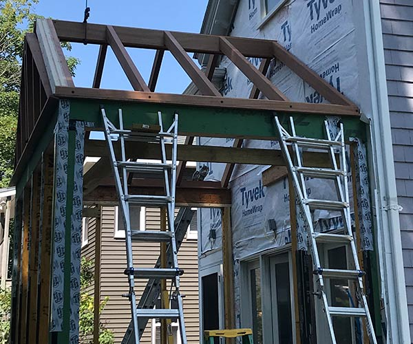 Ladders left by workers are stacked against the side of a brand new home addition that has just had new assemblies installed before mahogany trim and insulated glass are added