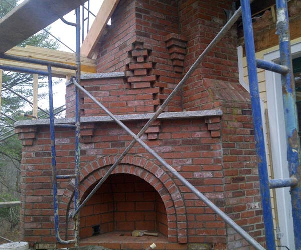 A red brick corner fireplace with an intricate design is under construction in this photograph