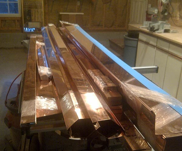 Copper caps and flashing are stacked lengthwise inside the Sunspace Design workshop