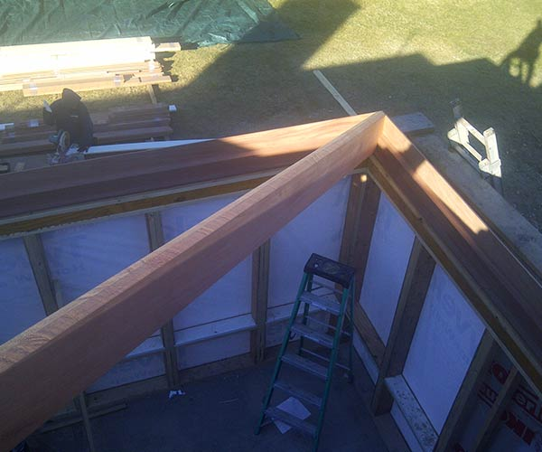 A look at the corner of a solid mahogany hip rafter that will comprise part of a Hamilton, Massachusetts glass conservatory's intricate roof system frame
