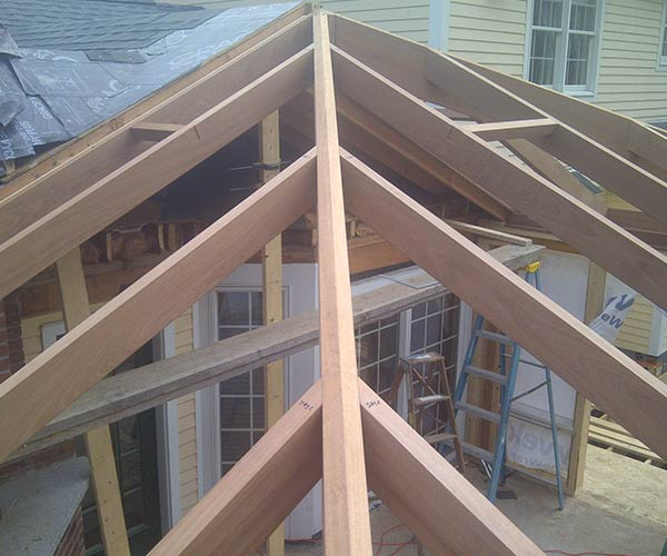 The mahogany glass roof frame for this custom project is starting to take shape, with framing elements visible before the start of glass installation