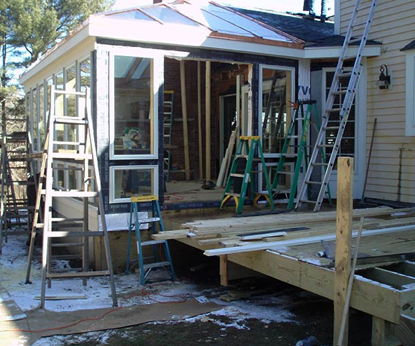 An assortment of construction ladders are positioned near a conservatory that's under construction; Andersen 400 series windows are being installed