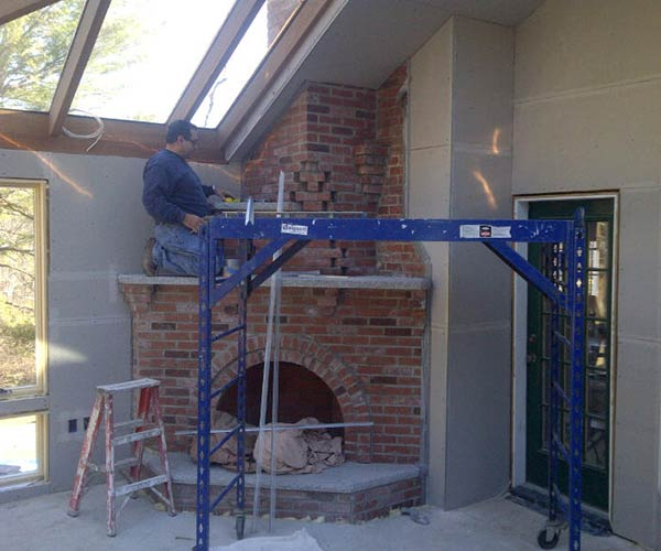 A crewman applies mesh and edge protection to the joints of a corner fireplace