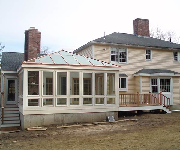 The exterior of a finished conservatory located to the side of a client's home before paint work is completed