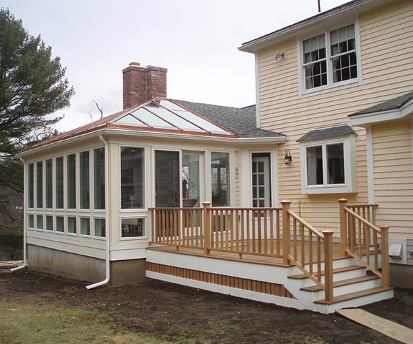 A view of the new deck adjacent to a glass conservatory with French doors; the deck is IPE, railings and balusters are cedar wood