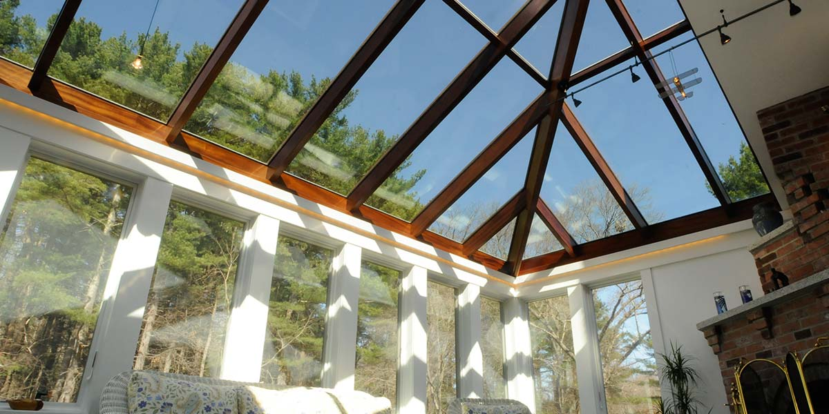 The glass roof of this conservatory is framed in mahogany and features an interesting, angular design that catches the eye