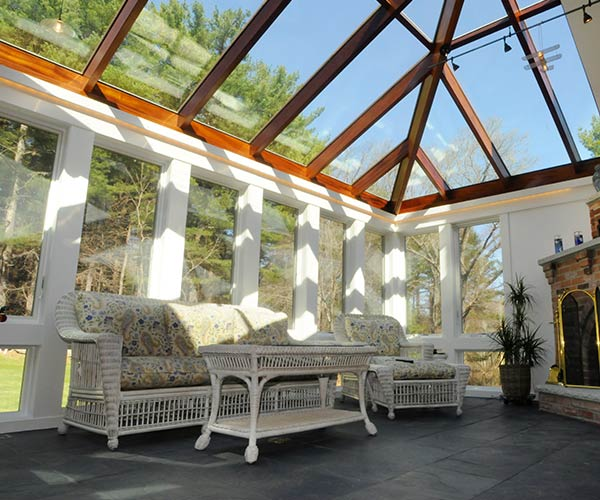 Seating furniture inside this conservatory sits atop a slate floor that has been outfitted with interior heating mats for added comfort