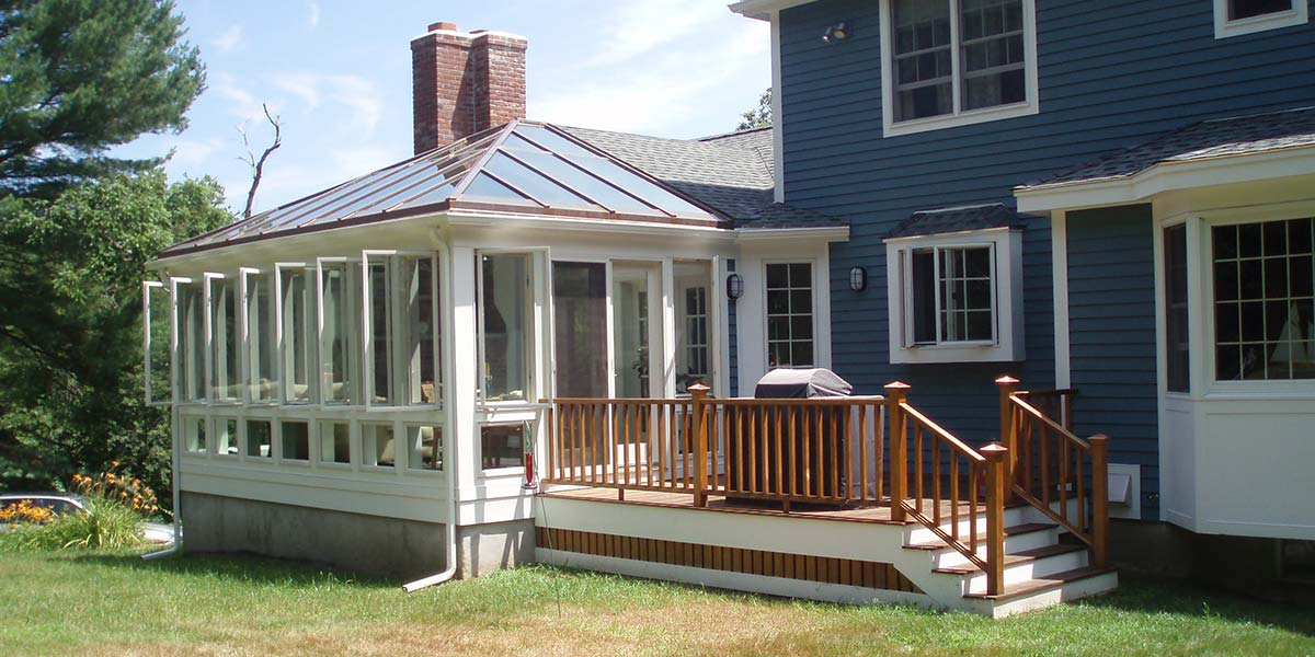 The windows of this completed conservatory are open to allow fresh air inside; the neighboring deck is complete and houses a home grilling station
