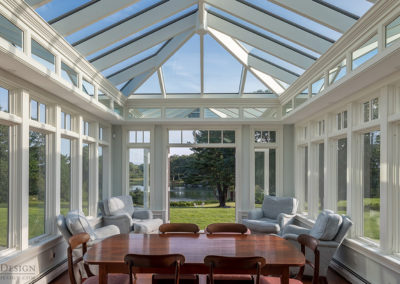 A view over the top of a shining dinner table and through the French Doors of this custom glass conservatory, revealing a river in the distance