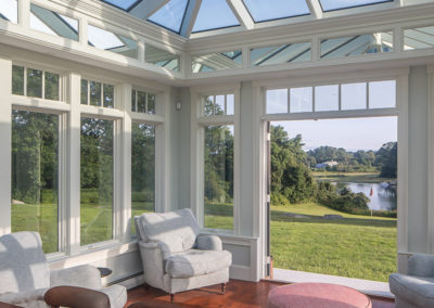 A luxurious conservatory interior with exquisite detailing along the walls, and picturesque tall windows