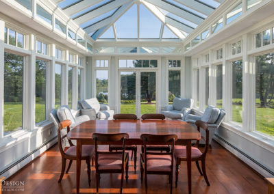 A full dining space is set up inside this custom glass conservatory located in Maine