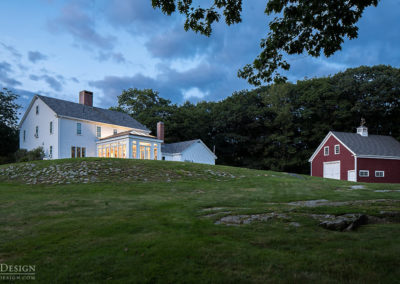 A white home with a brand new classic glass addition stands proudly atop a hill at dusk