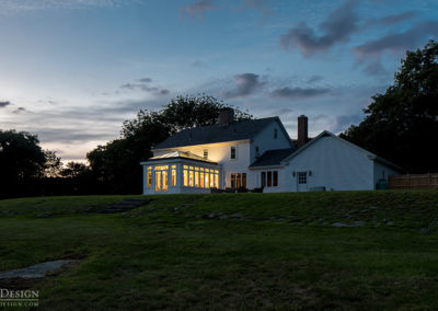A custom engineered glass conservatory stands beside the home it has been annexed to at the top of a Maine hill at dusk