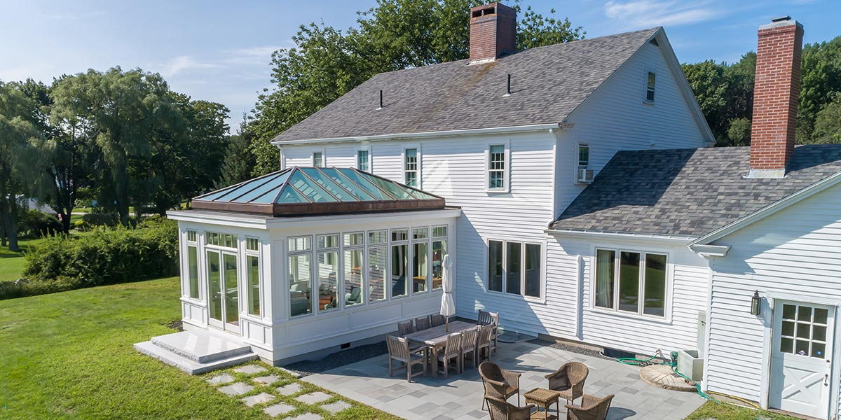 An outdoor patio area and custom glass conservatory located to the rear of a beautiful Maine home