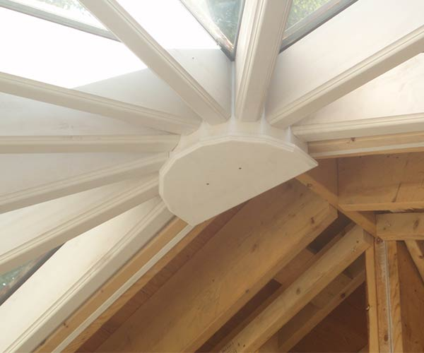 A view of the custom glass conservatory's recently positioned ridge and kingpost