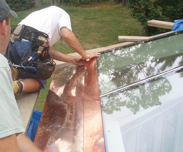 As the sun goes down, work on glass installation for this roof system winds to a close