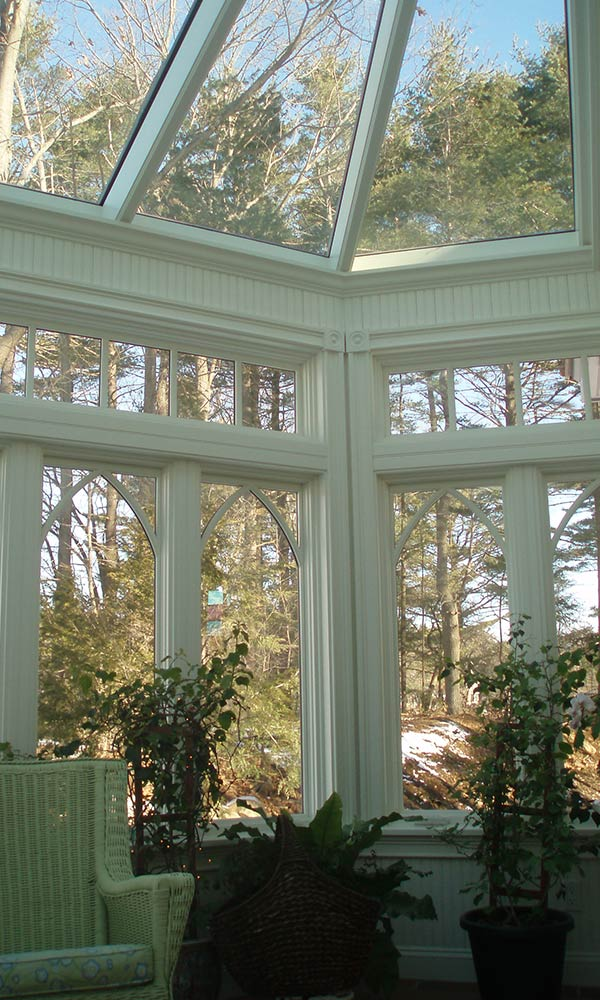A photograph taken from the interior of a glass conservatory that's still under construction depicting conventionally built wall framing and LVL headers