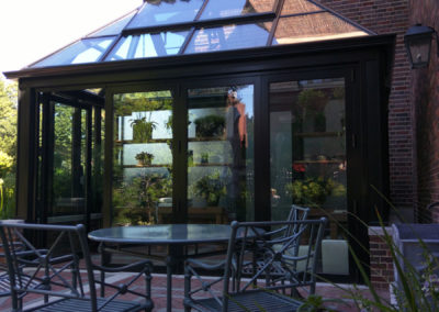 A black powder-coated aluminum greenhouse with a glass roof, ridge cresting, and outdoor seating area glimmers in the sun in Boston, Massachusetts