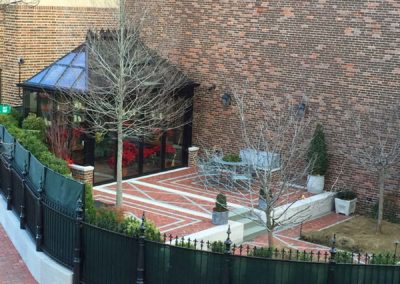 A wrought-iron fence wraps around a red brick outdoor platform upon which a custom Sunspace Design glass and aluminum conservatory sits