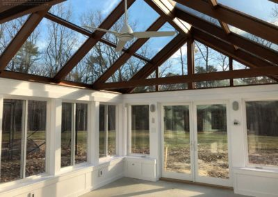A recently completed York, Maine greenhouse working space with solid concrete flooring, lighting fixtures, and a gorgeous mahogany-framed roof system