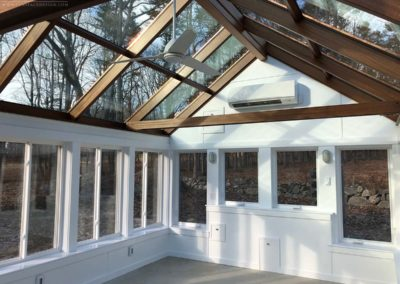 A well-insulated greenhouse with pristine white walls, mahogany-framed glass roof elements, tall windows, and an HVAC system for heating and cooling