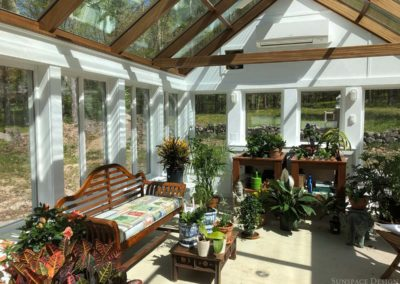 A York, Maine greenhouse illuminated by the midday sun is full of life with multiple shelves, a colorful bench, countless lush plants, and other decorations