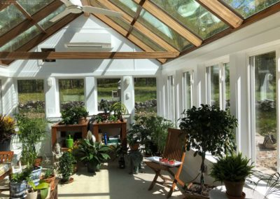 Lush vegetation fills the interior space of a custom engineered greenhouse as bright shafts of sunlight enter through large glass roof panes and tall windows
