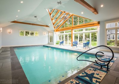 A close view of the exterior of a pool enclosure with tall windows, sliding doors, and a stunning glass roof centerpiece