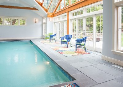 A pool enclosure building with additional accomodations including a seating area, bathroom, and kitchen