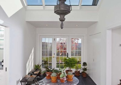 Light shines through insulated glass of a custom, mahogany-framed ridge skylight into the plant-filled foyer area a New York home