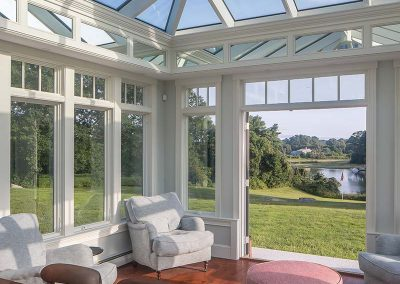 Shafts of light enter a conservatory space through a massive angular glass roof above as a nearby river is visible through tall glass windows and opened French doors